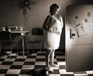 Pregnant woman eating from the refrigerator with door open