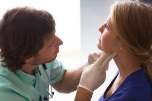GP examining young woman, who has problems with throat