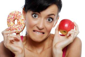 Young woman deciding between an apple or doughnut.