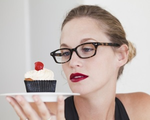 Woman eyeing a cupcake.